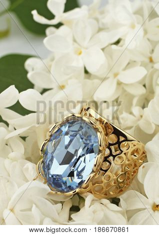 Ring with gemstone on white flower background