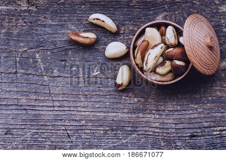 Tasty Brazil nuts from Bertholletia excelsa tree in wooden bowl on the old background with place for text. Healthy edible seeds food ingredient on the table. Top view. Copy space.