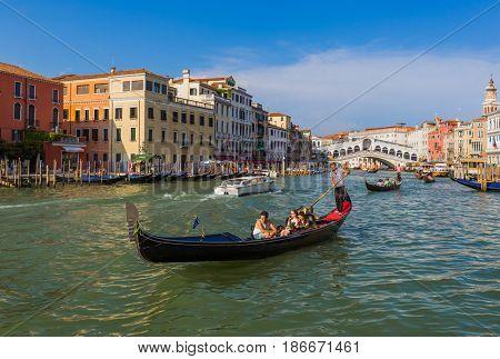 VENICE, ITALY - AUGUST 21, 2016: Tourists ride in gondola near Rialto bridge on August 21, 2016 in Venice Italy.