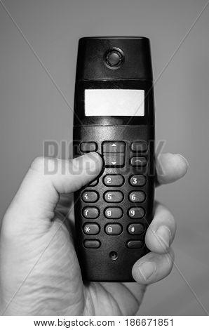Hand holding a home telephone. Black phone