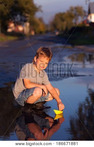 boy play with autumn leaf ship in water, chidren in park play with boat in puddle.