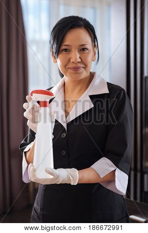 Absolutely clean. Pleasant good looking nice hotel maid holding the cleansing agent and showing in to you while using it for work