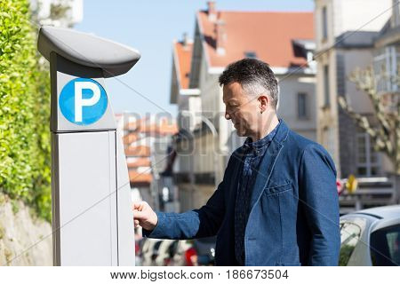 Man using parking meter, Biarritz, France. Man pays for Parking