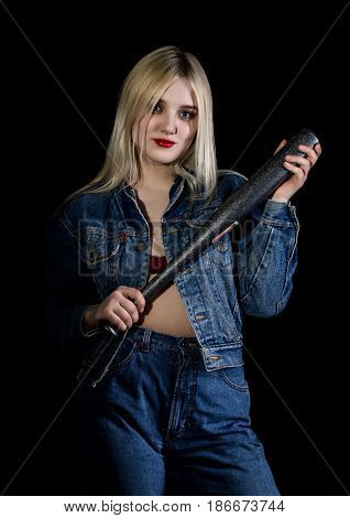 Criminal young woman with baseball bat, young hooligan in jeans and a denim jacket.
