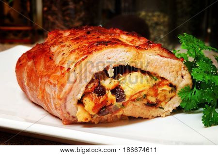 Roasted pork loin with apple-raisin stuffing on a platter in a home kitchen