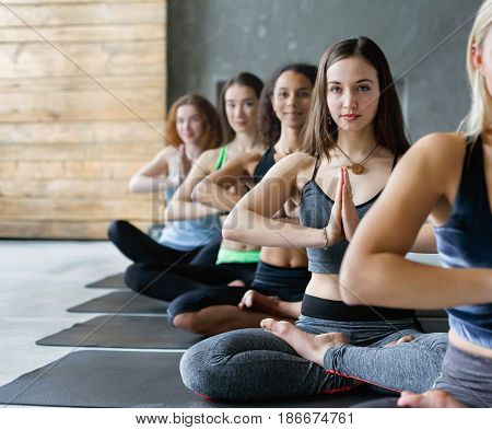 Group of people in yoga class, meditation lotus pose. Young women relaxation. Healthy lifestyle in fitness club