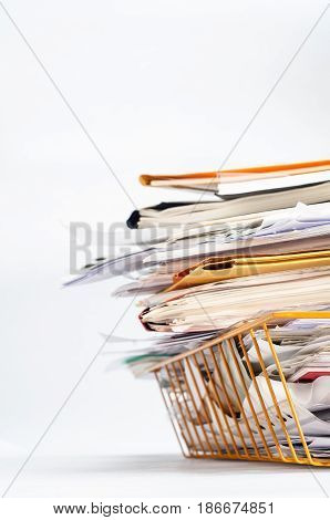 Angled shot of a yellow wire office filing or in tray stacked high with a messy pile of documents. Copy space on white background to left and above.