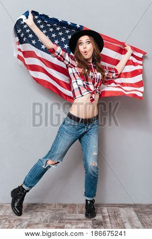 Full length portrait of a patriotic cheerful girl holding USA flag and looking at camera isolated over gray background