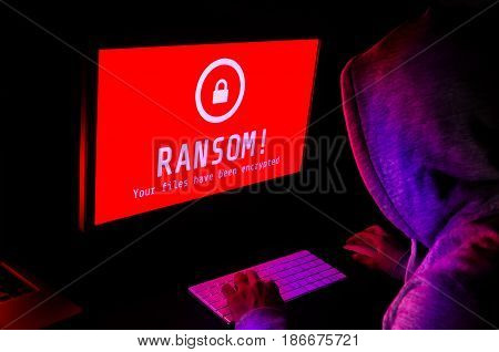 Computer screen with ransomware attack alert in red and a hacker man keying on keyboard in a dark room ideal for online security failure and digital crime