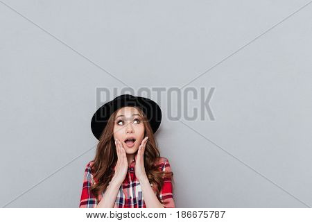 Portrait of a young shocked casual woman in hat holding hands at her face and looking away at copyspace isolated over gray background