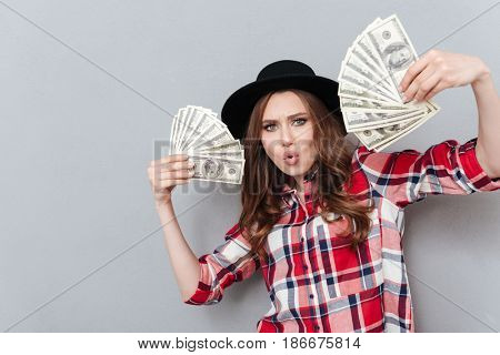 Portrait of a young casual girl holding money banknotes isolated over gray background