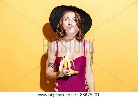 Portrait of a lovely young girl in summer hat and swimsuit chewing bubble gum and holding banana isolated over yellow background
