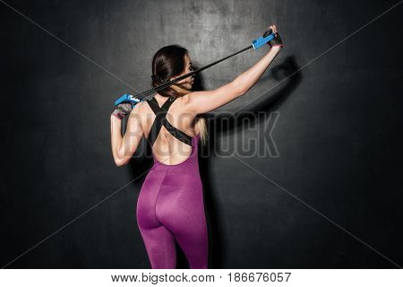 Back view of young hardworking woman using hand expander isolated over grey