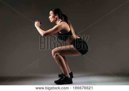 Photo of strong sportswoman make sports exercises over grey background. Looking aside.