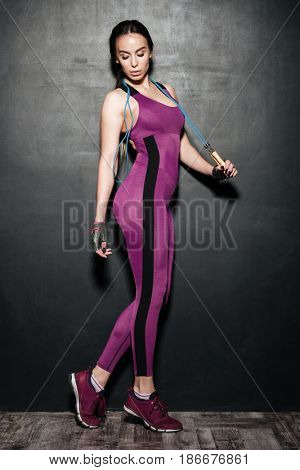 Photo of concentrated sports young lady standing and posing over black wall. Looking aside while holding skipping rope.