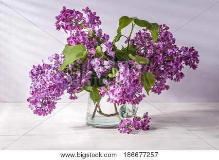 Still life with lilac flowers in glass vase on table