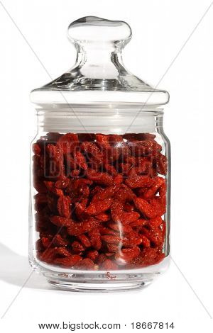 goji  berries wolfberry in glass jar, bright color, white background and ligth shadow