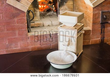 Flour spilling out of a wooden windmill on the background of a Russian stove.