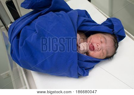 childbirth baby asian girl wrapping cloth with blue fabric after born in Maternity ward