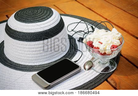 Glass bowl with raspberry and whipped cream smartphone headphones and summer hat