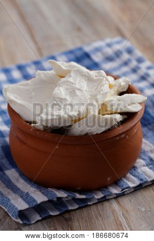 Cottage cheese in a pot on a rustic table