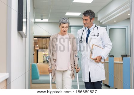 Mature doctor helping old female patient in crutches at the hospital. Physical therapist helping a woman on crutches in a medical clinic. Professional doctor and senior patient walking in hallway.