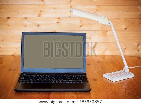 Place of work with notebook on table and lamp.