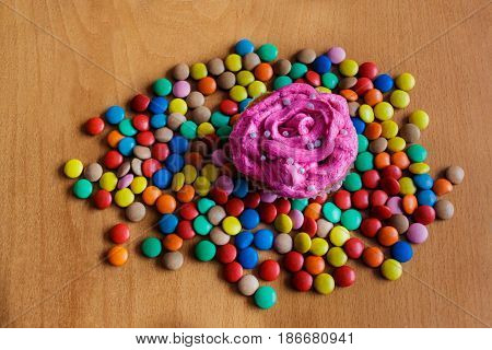 Homemade cupcake and candies over wooden background
