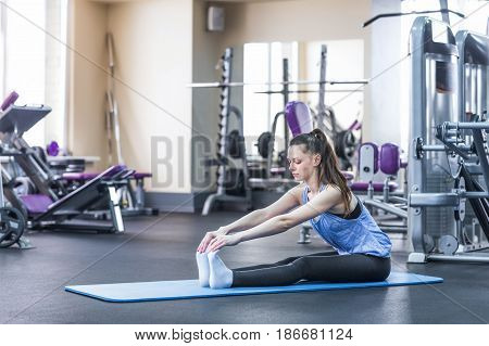 Portrait of happy young woman doing stretching exercise in gym.