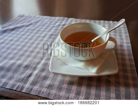 Cup of tea on a blue checkered tablecloth