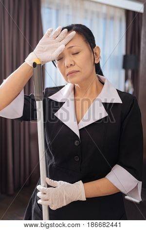 So tired. Hard working nice Asian chambermaid holding a mop and having her eyes closed while being exhausted
