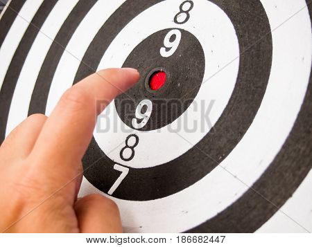 Black and white dartboard with hand point at center (Concept for target achievement business focus)