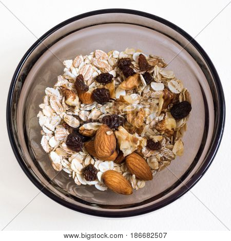 Delicious breakfast muesli with oat and wheat flakes mixed with raisins and nuts served in a brown glass bowl for a healthy meal