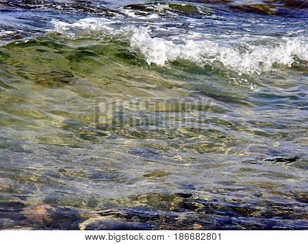 The wave rolls to the shore. Colorful stones under transparent water. Low DOF photography. Shallow water, sun glare. Sea foam. Black Sea near South Ozereyevka, Novorossiysk, Russia.