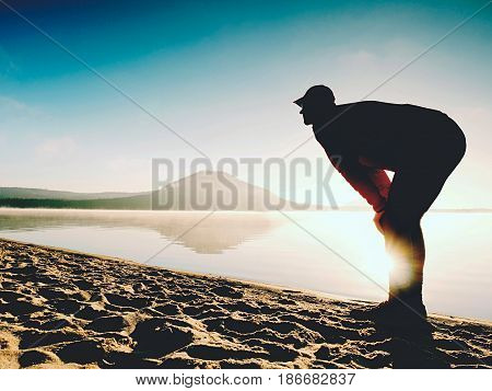 Man Exercising On Beach.  Silhouette Of Active Man Exercising  And Stretching At Lake