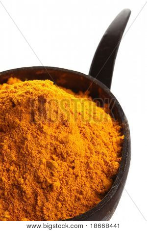 spices - pile of bright yellow ground TURMERIC in coconut bowl, isolated on white
