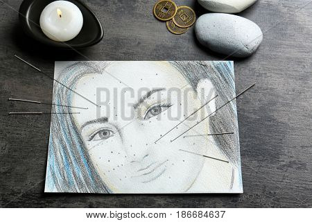 Acupuncture needles, portrait drawing and stones on table