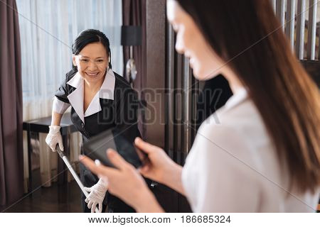 Professional housekeeping service. Positive good looking nice chambermaid cleaning the floor and smiling while standing near the hotel manager