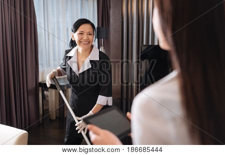 Hotel housekeeping. Positive delighted chambermaid smiling and looking at her manager while cleaning the room