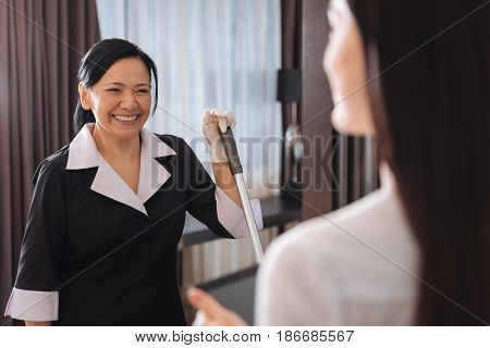 I cleaned everything. Happy positive nice chambermaid holding a mop and smiling while looking at the hotel manager