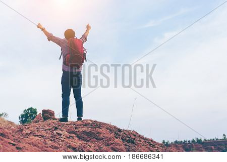 Hiking man rock climbing climber or trail runner in mountains inspirational landscape. Motivated hiker with red backpack looking at beautiful view. Trekking travel and tourism concept. Fitness
