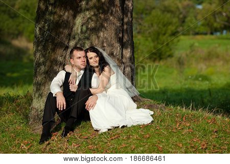 Gorgeous Bride Leans On Groom's Shoulder While Sitting Beneath An Old Tree