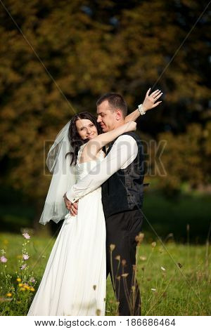 Bride Smiles Broad While Leaning To A Groom And Twining Her Hands Around His Neck