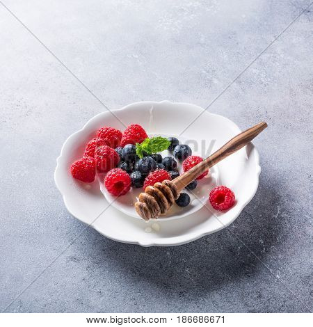 Freshly blueberries and raspberries on white plate with honey. Healthy eating and nutrition concept with copy space.