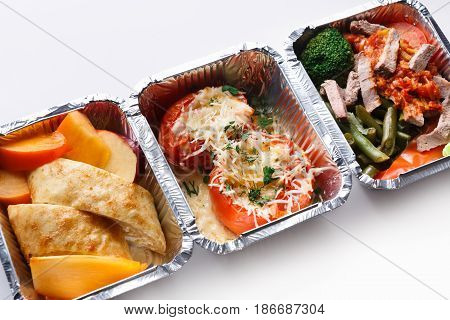 Healthy food in lunch boxes on white background. Eating right concept. Fresh diet daily meals delivery. Vegetables, meat and fruits on wood