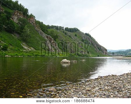 A quiet backwater of a mountain river, against the backdrop of a remote farm