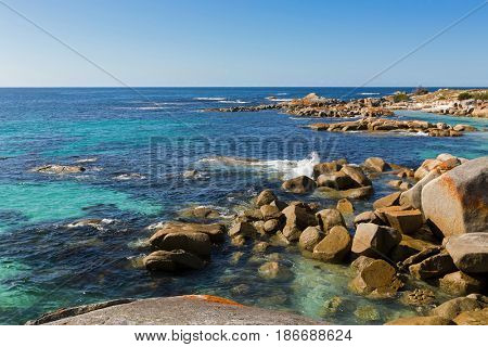 Waves splashing rocks at Bay of Fires in Tasmania. Colorful fiery red orange lichen growing on granite rocks formations, rocky coastline in Australia