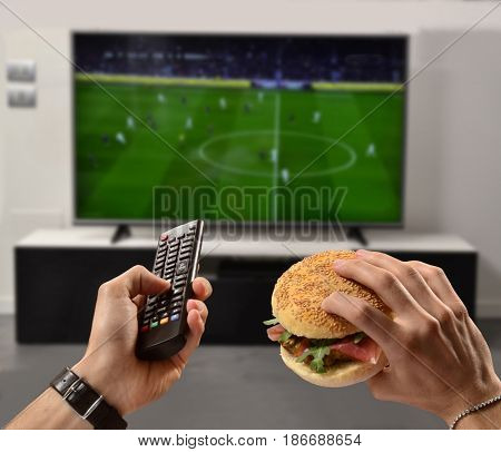 In front of television eating burger holding a remote control.