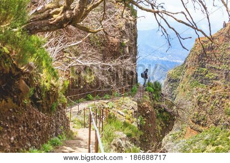 trekking on Madeira island. A route between two peaks Pico Ruivo and Pico do Areeiro. Amazing cliff view with tourist on the edge