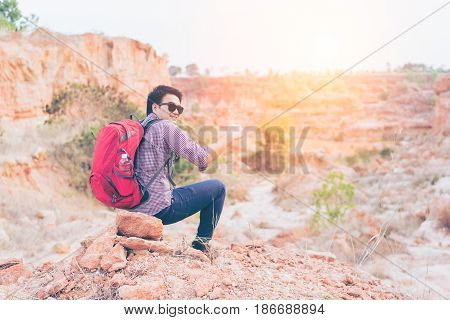 Hiking man rock climbing thumbs up action climber or trail runner in mountains inspirational landscape. Motivated hiker with red backpack looking at beautiful view. Trekking traveler concept